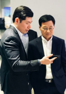 Anthony Tan Grab CEO shows Lee Sangchul Samsung SEA Oceania President an CEO the Grab app